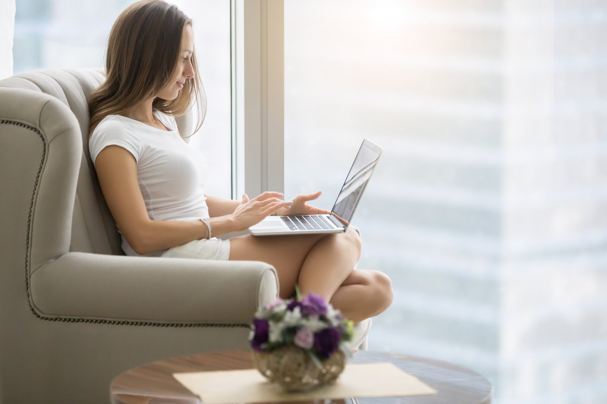 young woman sitting in armchair with laptop PSVFPU7